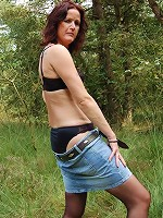 Horny brunette stripping off her clothes outdoors.