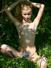 Pretty blond girl posing topless in the fields