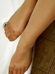Red-haired chick tenderly touching her feet while fitting on new pantyhose